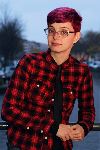 Photograph of Corinne Duyvis, a lightskinned, 20ish person with short red hair, metal framed glasses wearing a red and black plaid shirt and a black tie. A blurry outdoor background of water, boats and trees is behind.